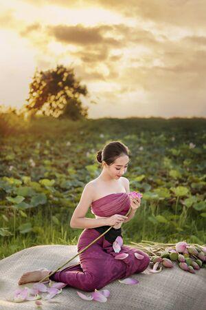 beautiful woman in traditional asian dresses harvesting water lilies in garden Foto de archivo - 128099659