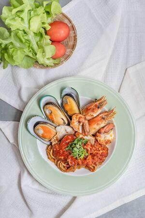 Spaghetti with seafood in tomato sauce on a plate Foto de archivo - 128099800