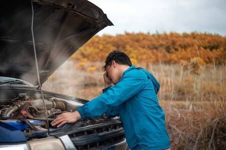 Asian stressed man having trouble with his broken car looking in frustration at failed engine Foto de archivo - 128100499