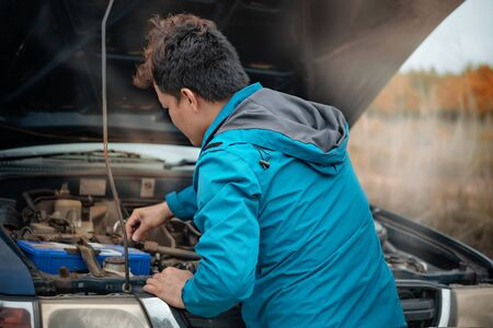 Asian stressed man having trouble with his broken car looking in frustration at failed engine Foto de archivo - 128100508