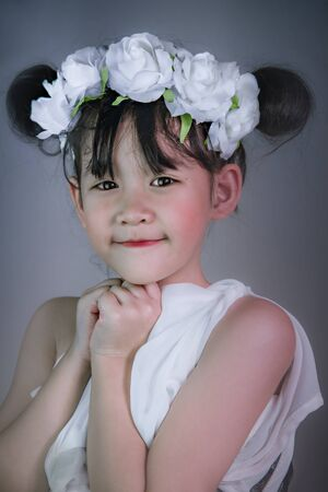 Cute asian little girl with wreath of flowers on her head