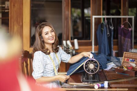 Beautiful asian dressmaker in workroom .designer woman keeping arms crossed and looking at camera with smile while standing in workshop Banco de Imagens