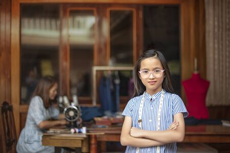 asian little girl dressmaker keeping arms crossed and looking at camera with smile while standing in workshop Banco de Imagens