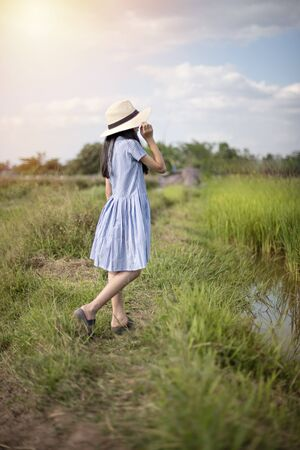Asian cute girl with hat in green field and blue sky background