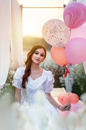 portrait of beautiful girl with balloon in nature field