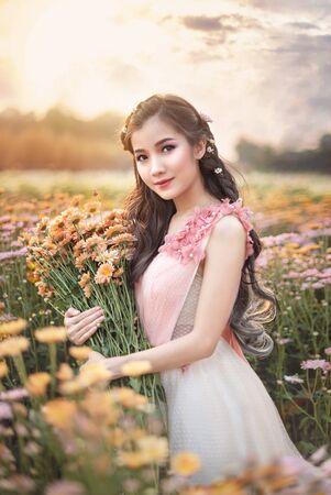 portrait of beautiful asian woman in nature flowers field Banco de Imagens
