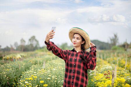 portrait of beautiful asian woman in nature flowers field. happy farmers concept Banco de Imagens