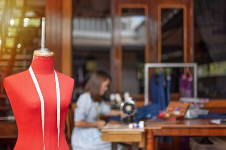 Red dummy with measuring tape in tailors studio. sewing workshop,