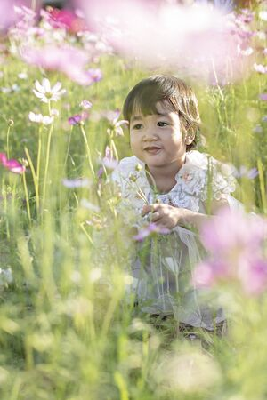 cute asian children girl in nature flowers field