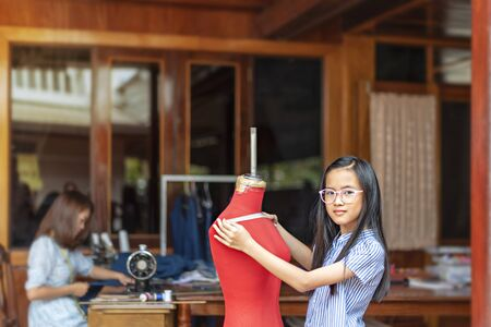 asian little girl dressmaker measuring the  dummy and looking at camera with smile while standing in workshop
