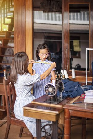 asian tailor working with measuring tape, dressmaker measuring girl in workroom