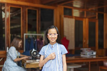 asian little girl dressmaker looking at camera with smile while standing in workshop Banco de Imagens