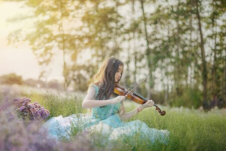 portrait of beautiful asian woman in nature flowers field with violine