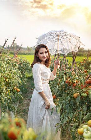 Asian pretty woman with white umbrella  in tomatoes garden