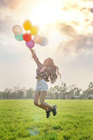 Portrait d'une jolie femme heureuse avec des ballons dans un champ vert