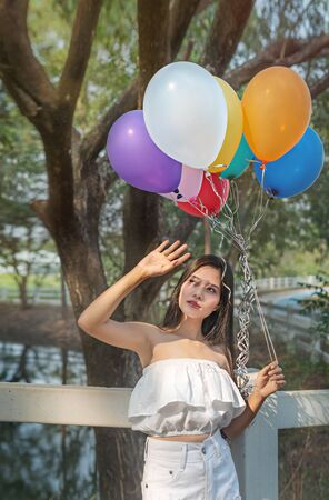 Portrait of asian pretty woman with balloons in green garden