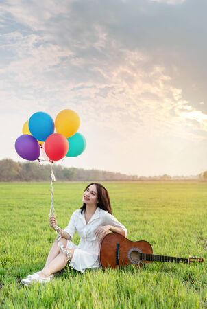 Portrait of a happy pretty woman with balloons relaxing  in green field