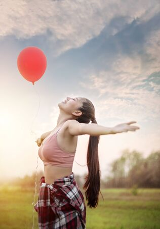 Portrait of a happy pretty woman with balloons in green field