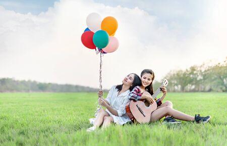 Portrait of  happy two women relaxing in green field Banco de Imagens