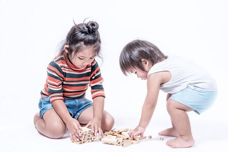 Two happy siblings playing a game  with wooden box