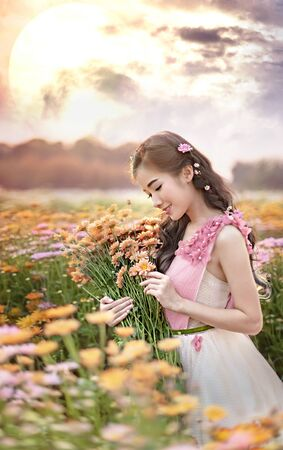 portrait of beautiful asian woman in nature flowers field Banco de Imagens