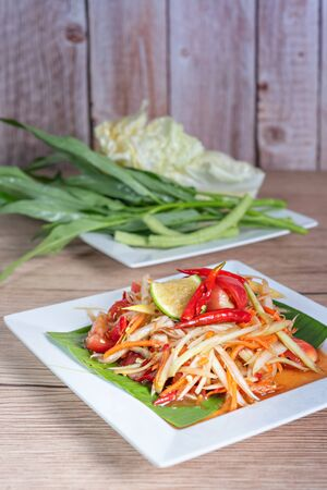spicy papaya salad on dish ,  favorite Thai food served with fresh vegetables