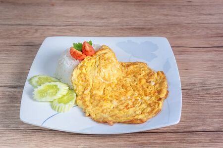 asian style omelet scrambled eggs over rice served with fresh vegetables on dish Banco de Imagens