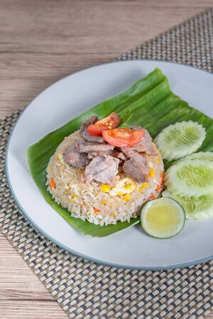 fried rice with pork served with fresh vegetables on dish