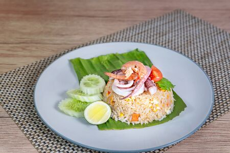fried rice with seafood served with fresh vegetables on dish