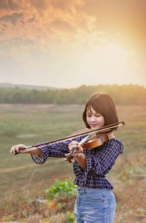 asian cute little girl with violin in field