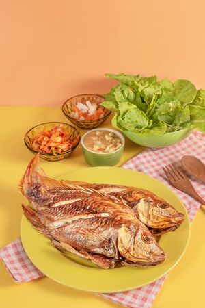 Fried fish dishes served with asian style sauce  , pickled vegetables and fresh lettuce Banco de Imagens