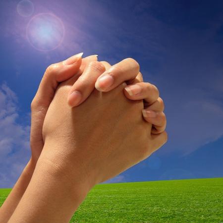 fede: Mano di preghiera con sfondo verde erba Archivio Fotografico