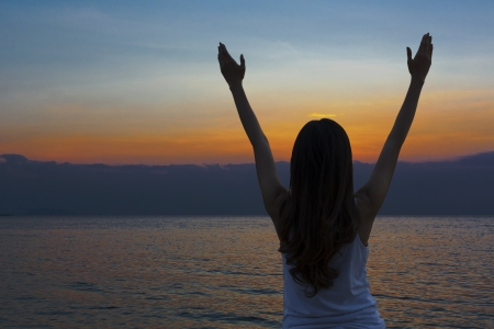 Young woman with arms raised in praise worshiping God Stock Photo