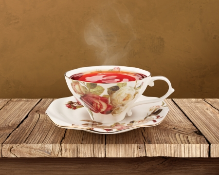 china rose: Porcelain tea cup over wooden table with clipping path Stock Photo