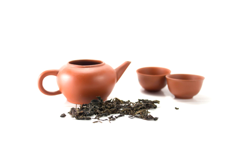 chinese tea pot: Isolated Chinese tea pot and tea leaves Stock Photo