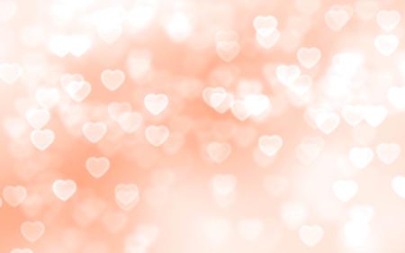 Bright peach color heart-shaped bokeh background Foto de archivo