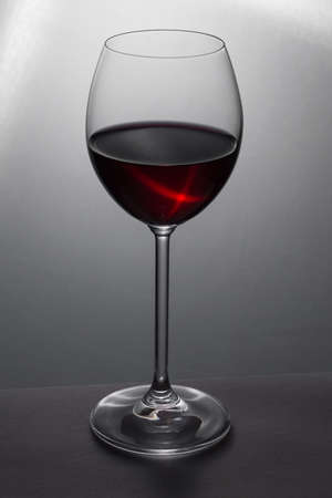 Beautiful glass of red wine on grey
