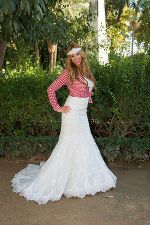 photography session: Blonde woman wearing a wedding dress with a plaid shirt Stock Photo