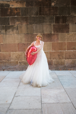 photography session: Blonde bride posing with abig heart Stock Photo