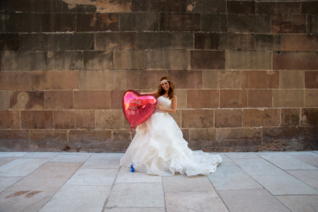photography session: Redhead bride posing with a big heart