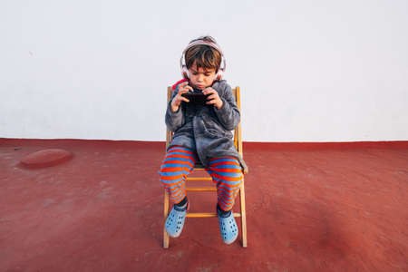Portrait of five years old child with smartphone and headphones listening to music and playing a video game 免版税图像