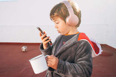 Child with a smartphone drinking coffee at breakfast while using his mobile phone to call, chat and read the news Stockfoto