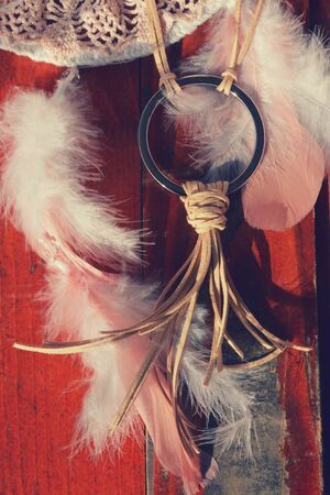 Indian jewelry leather earrings with dreamcatcher and feathers on the wooden background fashion.