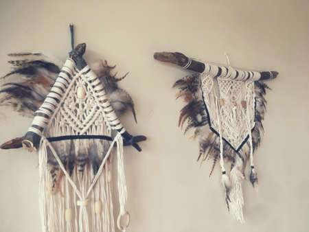 Handmade wall hanging white color with feathers. Home decor photo