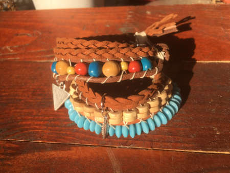 Wrapped native American bracelet, urban tribe jewelry on the wood background. Banco de Imagens