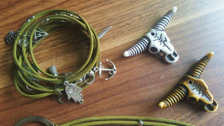 Fashion handmade jewelry photo olive green color with feathers and bull skull. Archivio Fotografico