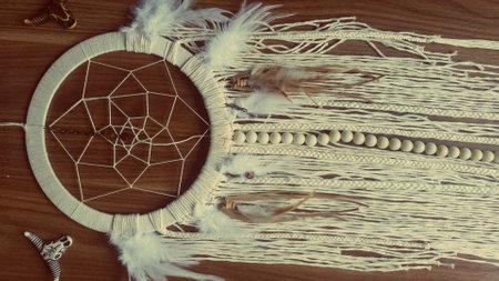 Dreamcatcher home decor white color on the wood background. Native American art. Foto de archivo