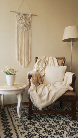 Home decor photo, Boho style room with Macrame wall hanger, lamp, chair and desk.
