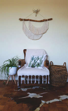 Home decor photo, Boho style room with Macrame wall hanger, basket and chair