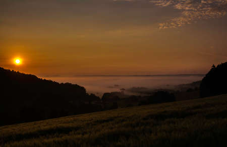 A valley in the fog at sunrise